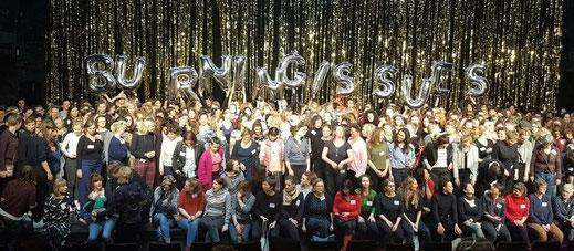 Die Teilnehmer:innen von Burning Issues haben sich vor einem Glitzervorhang zu einem Gruppenfoto vesammelt