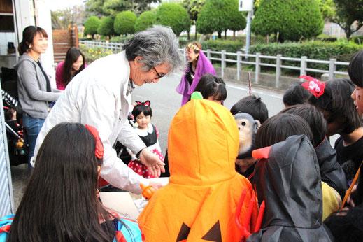 ハロウィンで子供たちにお菓子を配る社長