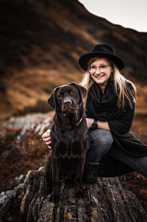 Schoko Labrador in den Bergen mit seiner Besitzerin im Hintergrund, fotografiert von der Ostschweizer Hunde Fotografin Monkeyjolie