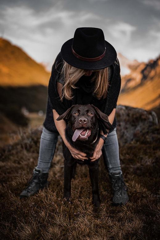 Labrador Retriever mit raushängender steht zwischen den Füssen seiner Besitzerin im Hintergrund, fotografiert von der Ostschweizer Hunde Fotografin Monkeyjolie