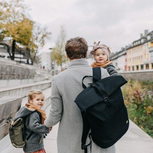 Vater mit Wickelrucksack schwarz und Tochter