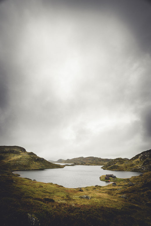 a cabin at a lake on a cloudy day in the highlands