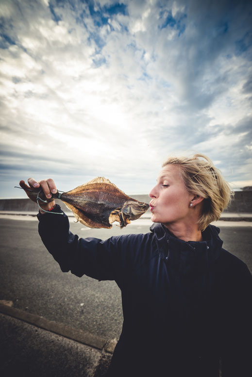 A blonde girl kissing a dried fish