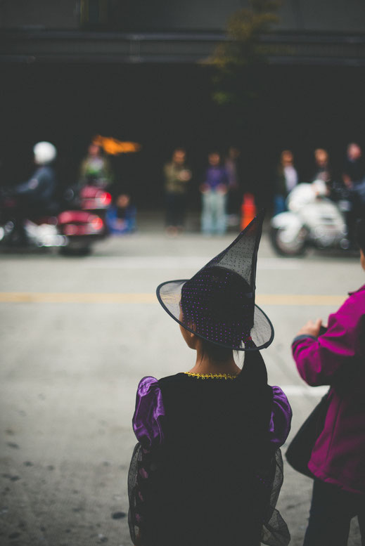 a girl in a wizard costume watching a Halloween parade