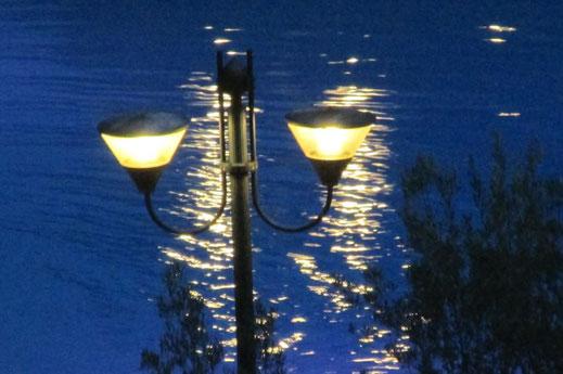 """Dieses Foto zeigt Laternenlicht über einer Wasseroberfläche. Das Bild dient als Ideengeber für den Song """"Sleepy Lagoon"""" von The Platters."""