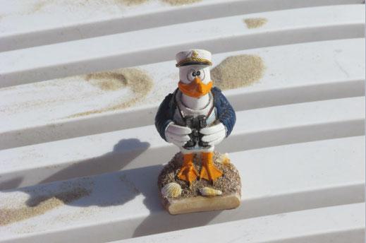 Dieses Foto zeigt eine Souvenir-Figur. Es handelt sich um eine Ente im Matrosenanzug. Solche Stücke werden auch als Kitsch bezeichnet. Nippes und Tinnef sind verwandte Begriffe.