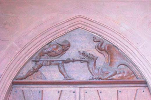 Dieses Bild zeigt den Kmapf eines Ritters mit einem Drachen. Foto vom Fries einer Kirche in Freudenstadt.