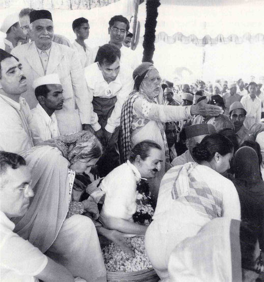September 1954, Ahmednagar, India : Meher Baba giving prasad to the passing crowd of followers, Papa standing with black cap & observing.