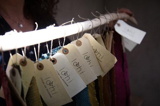 Rangée d'étiquettes au nom de lohi attachées a des cuirs avec quelqu'un en arrière plan