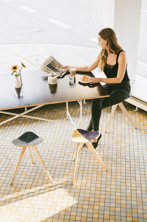 hocker an einem tisch in modernem ambiente. Gelungenes interior design. Hocker für den Esstisch oder für ein Cafe.