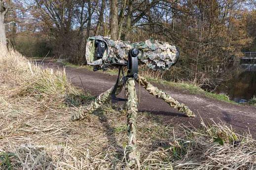 kamera und stativ mit tarnueberzug