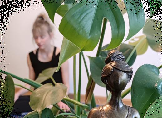 Blondes Mädchen meditiert mit Pflanze