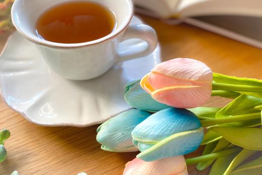 ピンクの懐紙に載せられたストロベリーチョコとピンクのバラのつぼみ。湯気の立つコーヒーカップ。パソコンのキーボード。。