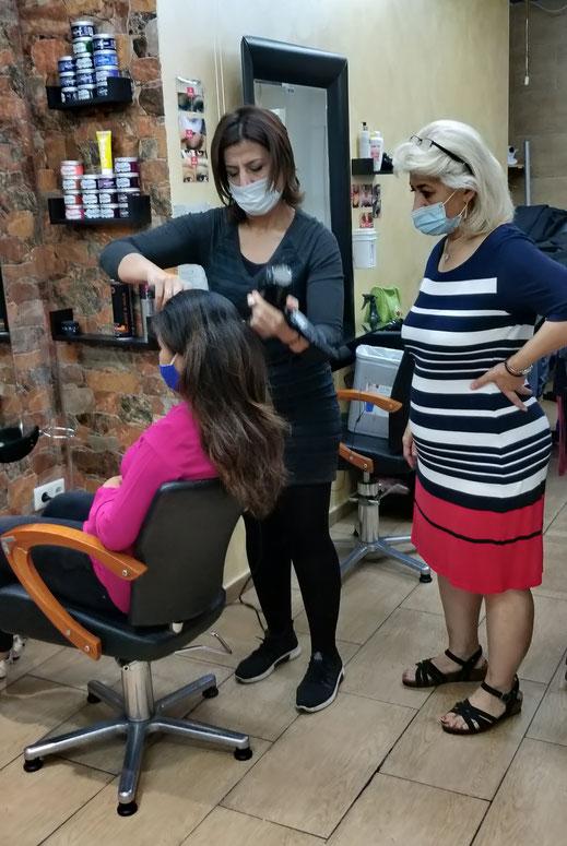 Auszubildende Hevin fönt einer Kundin unter Aufsicht der Meisterin die Haare