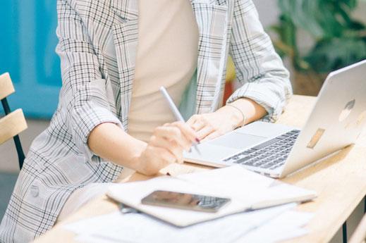 ノートパソコンのキーボードの上に置かれたサインペンとスマホ。