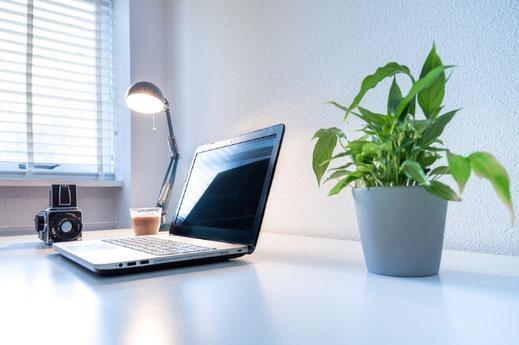 花柄模様の2冊のノート。コーヒーの入ったカップ&ソーサ。ゼムクリップとピンクの封筒。白のチューリップ。