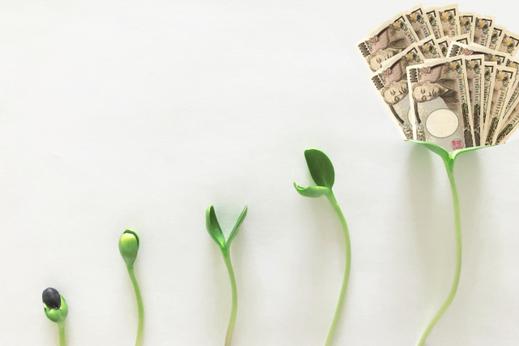 パソコンの横に置かれた経済新聞と電卓。眼鏡、ボールペン、ノート。