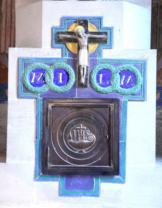 Une croix d'autel au-dessus du tabernacle avec sa porte en cuivre