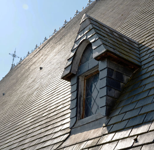 Lucarne en bâtière sur le toit de la cathédrale avec des ardoises toutes neuves