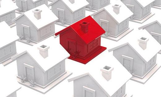rotes Haus inmitten von grauen Häusern