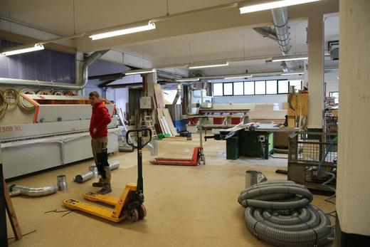 """in diesem Teil der sehr geräumigen Produktionshalle wird gerade eine """"Kantenanleim-Maschine"""" installiert"""