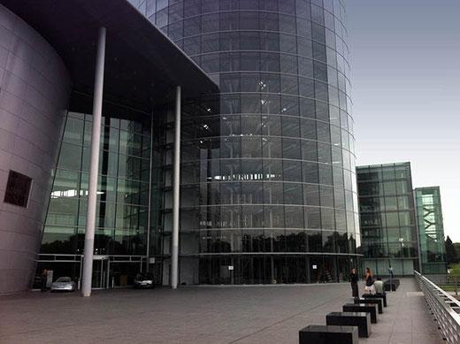 L'usine transparente VW. À gauche, devant l'entrée, un concept car. La tour ronde est un parking vertical équipé d'un élévateur robotisé.