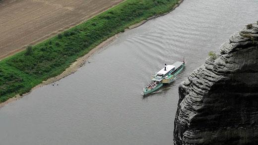 Vu de la falaise du Bastei, un bateau de croisière remonte le fleuve vers la frontière tchèque. C'est un navire ancien, à vapeur et propulsé par des roues à aubes latérales.