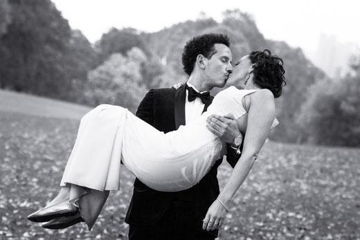Er trägt Sie am Aachener Weiher in Köln. Edles Hochzeitsbild in schwarz weiß.