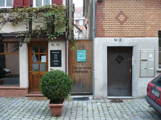 Die Eingangstüre befindet sich genau zwischen den Türen des Antiquitätenladens von Thomas Wiegand und der Tür des Haus Nr. 8. Im Hintergrund sieht man noch die Dachschräge der Werkstatt durchblitzen.