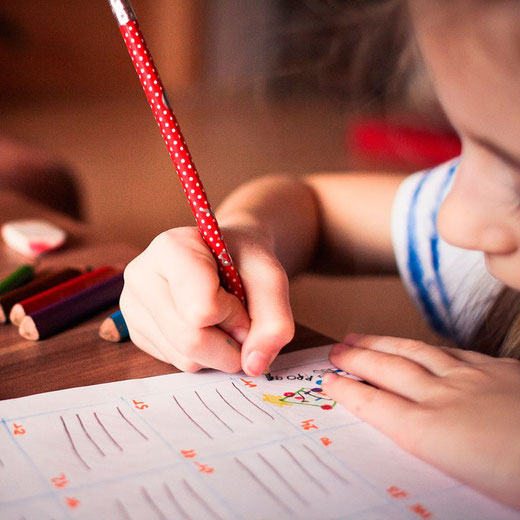 Kind übt mit einem Stift schreiben