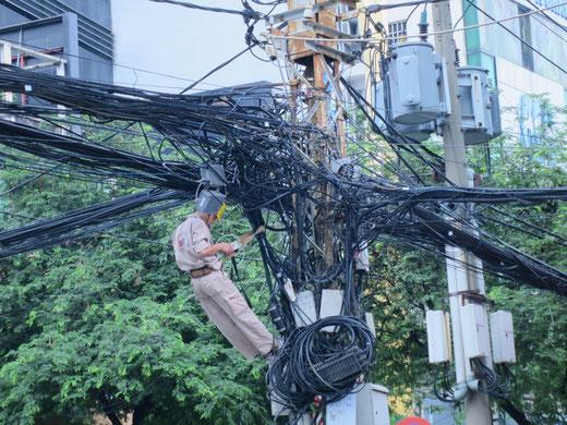 クモの巣のような配線を修理する人