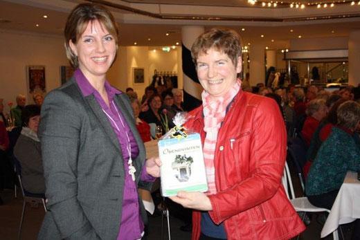 Hilde Wohlenberg bedankt sich bie der Referentin Gisela peters mit dem Dithmarscher Kochbuch