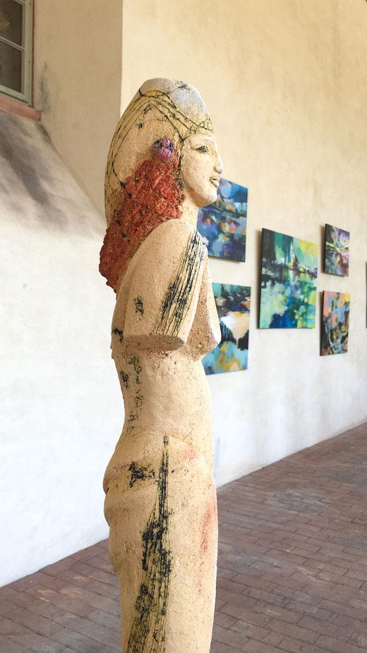 Keramikskulptur von Angelika Karoly, im Hintergrund Bilder von Liliana Geiss