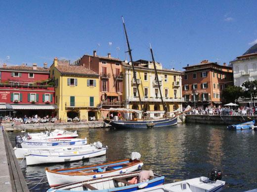 Der Hafen von Malcesine mit  Bars und Cafes und dem antiken Segelschiff