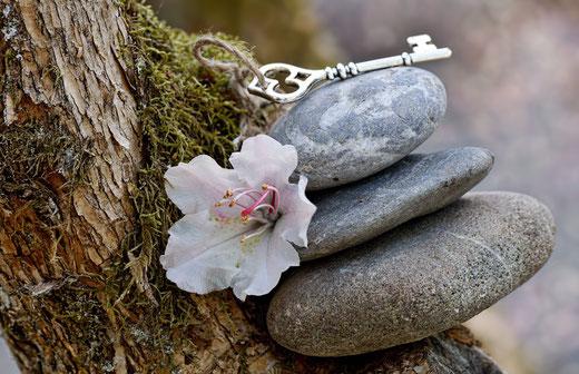 Drei graue Steine, eine rosa Blume und ein silberner Schlüssel