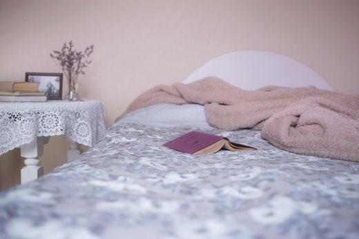 Bett mit Nachtkästchen und auf dem Bett liegt ein Buch