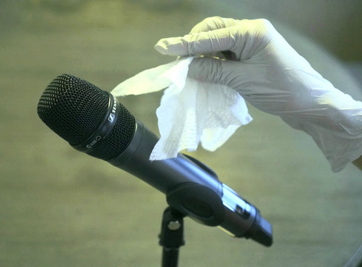 Handheld wireless microphone in a stand with woman's hand wearing a rubber glove holding a sanitizing wipe near the microphone.