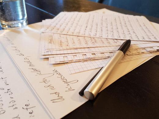 Auf diesem Bild zu sehen: Notizen, ein Stift, ein Schreibtisch, ein Glas Wasser und jede Menge Ideen zum kreativen Schreiben.