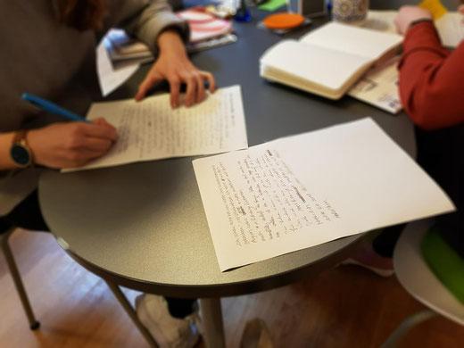 Menschen, die an einem Tisch sitzen und auf Papier schreiben.