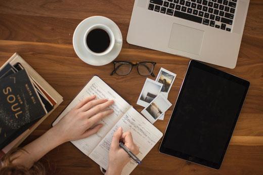 Ein Schreibtisch mit Laptop, Notzizbuch, Kaffeetasse, Brille, Büchern, Journal, schreibender Hand und mehr.