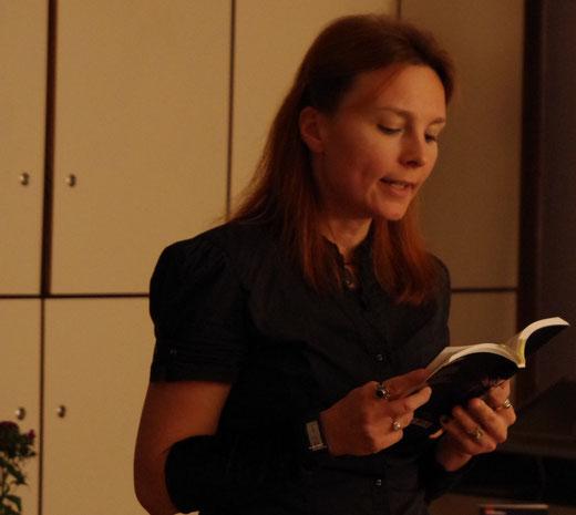 Frau liest aus einem Buch vor.