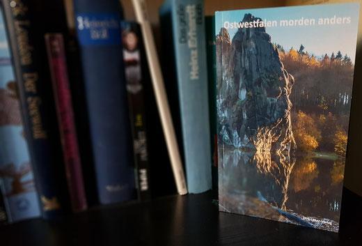 Cover des Buches Ostwestfalen morden anders im Dirk Laker Verlag vor anderen Büchern.