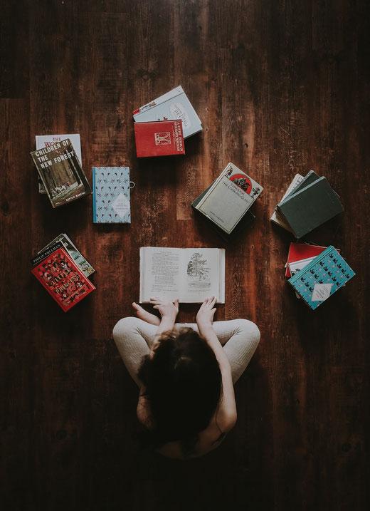 Hier seht ihr eine Frau, die von Büchern umgeben ist. Es geht um Kurse zum kreativen Schreiben.