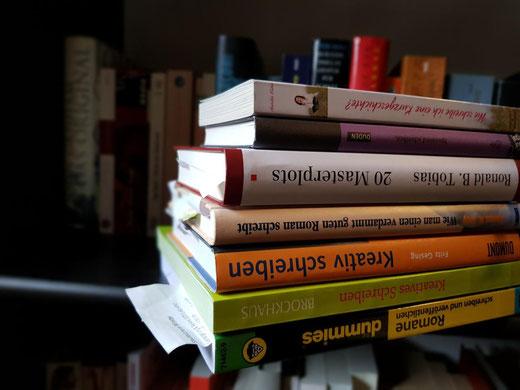 Hier sieht man einen Bücherstapel voller Schreibratgeber vor einem Bücherregal.