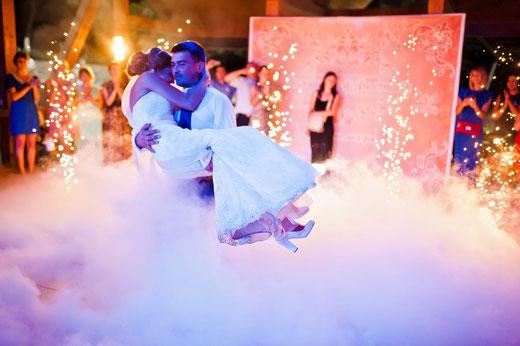 Bräutigam trägt Braut auf die Tanzfläche, die mit Bodennebel bedeckt ist auf Händen zu ihrem Hochzeitstanz