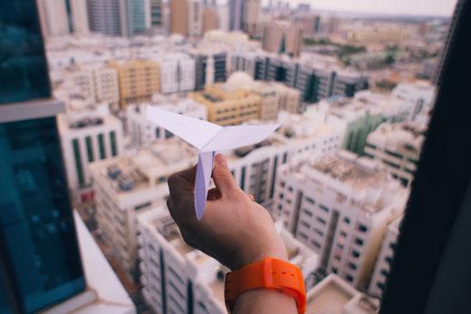 Papierflieger über der Stadt