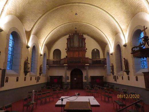 La nef et l'orgue sous l'éclairage plus intime des voûtes en briques.