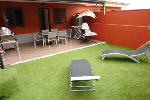 Im Vordergrund vom Bild sieht man die Sonnenwiese und im Hintergrund die Terrasse mit Grillbereich vom Ferienhaus.