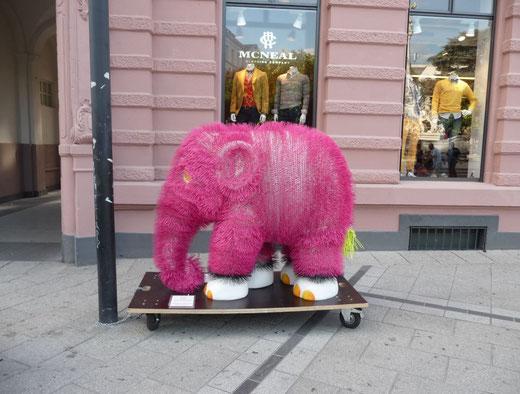 ein rosa Plüsch-Elefant auf einem Bürgersteig vor einem Kleidungsgeschäft