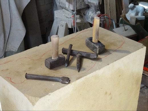 Sandsteinblock mit Steinmetzwerkzeugen. Sandsteinblock mit typischen Steinmetzwerkzeugen. Die Umrisslinien der Skulptur sind  bereits angezeichnet.